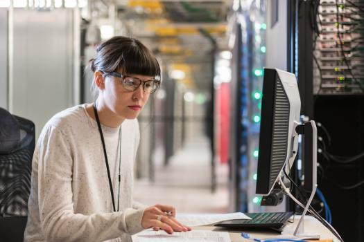 Woman with glasses working on a computer in a server room