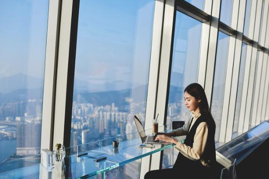 Woman with laptop in front of a cityscape