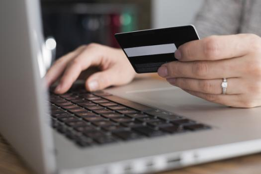 Image depicts online shopper holding credit card on laptop